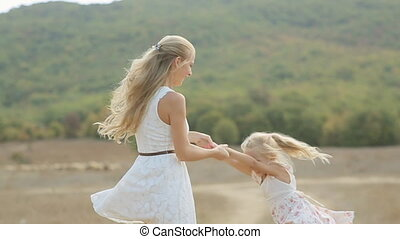 Charming mother circling happy little daughter in the field in slow motion