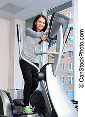 Beautifull female during exercise on a elliptical traner
