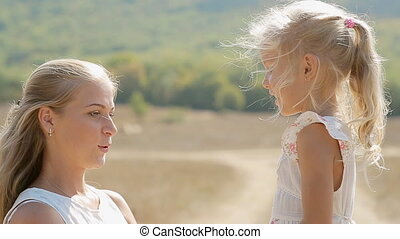Warm relations of mother and little daughter standing in the...