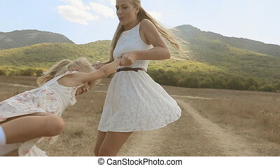 Joyful mother whirls little daughter, laughing and hugging her in slow motion