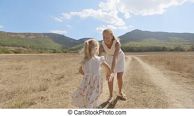 Beautiful mother whirls her little daughter on background of mountain slopes in slow motion