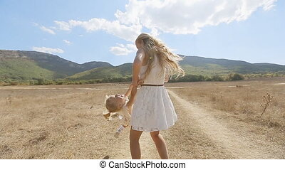 Beautiful mother whirls her little daughter on background of mountain slopes
