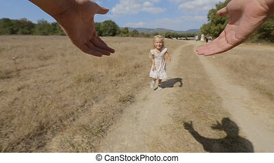 Carefree little girl is twirled around by father in the field