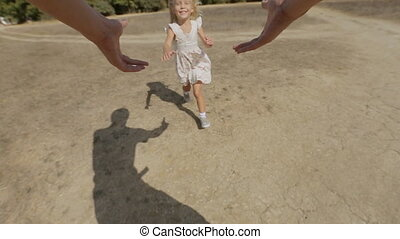 Carefree little girl is whirled by father in the field in...