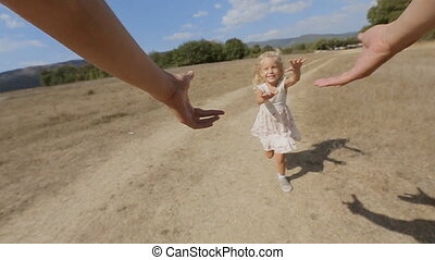 Cheerful little girl is whirled by father in the field in slow motion