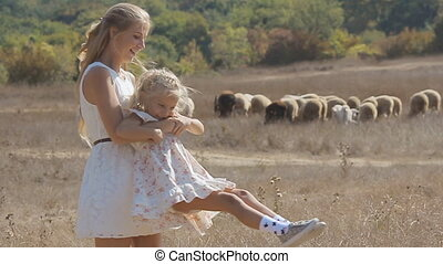 Young mother whirling her little daughter next to the flock of sheep in slow motion