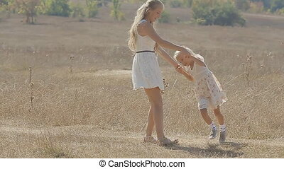 Young mother with long blond hair turns little daughter in the middle of the field in slow motion