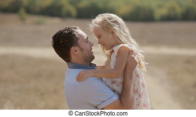 Dad raises his little daughter in arms and they hug and kiss...