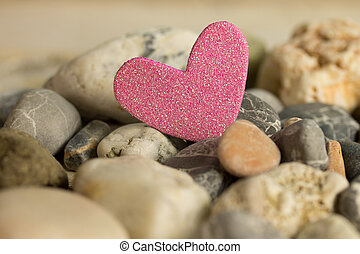 love - a pink heart between stones