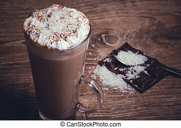 coconut hot chocolate in high glass on wooden background