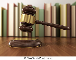 Wooden gavel and books on wooden table.