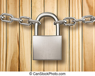 Locked padlock with silver chains isolated on wood...
