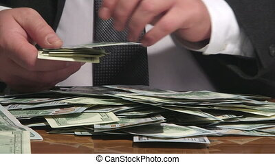 Business person sorting US 100 dollars bank notes at desk