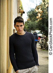 Handsome young man standing in European city street, leaning...
