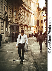 Handsome young man walking in European city street, an alley...