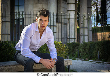 Handsome young man in European city, sitting on stone bench,...