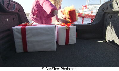 Shopper with shopping cart full of gift boxes loads car...