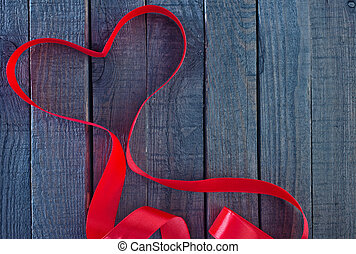 red ribbon - red heart ribbon on the wooden background