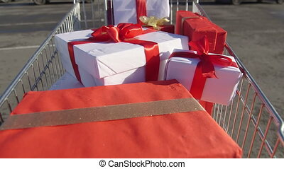 Shopper pulling shopping trolley full of gift boxes along car lot