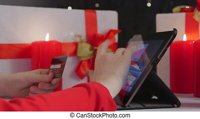 Girl using credit card and digital tablet computer for Christmas gifts buying online