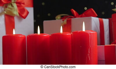Burning candles and gifts boxes under Christmas tree background
