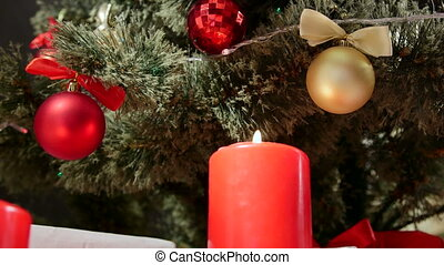 Burning candles under Christmas tree decorated with red and gold balls