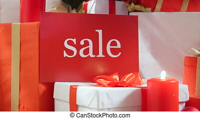 Christmas red white gift boxes with word Sale and burning candles