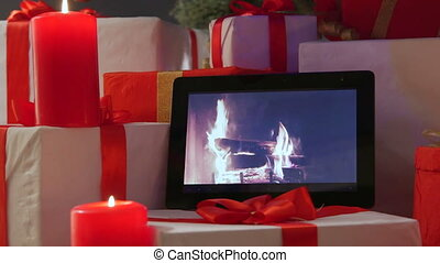 Burning candles gifts boxes and tablet computer with fireplace on screen under Christmas tree