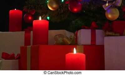 Burning candles and gifts boxes under Christmas tree at night background