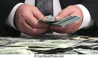 Business person counting bundle of US 100 dollars bank notes...