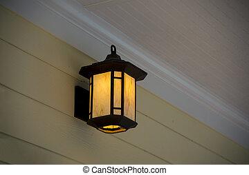 Porch Light - A white porch light against a brown vinal...