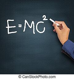 Hand writing theory of relativity (E=mc2) on a chalkboard