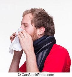 Man with runny noses neezes into a tissue - an with runny...