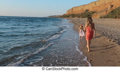 Mother with little daughter walking along the seashore leaving footprints on the sand in slow motion back viewMother with little daughter walking along the seashore leaving footprints on the sand in slow motion, back view