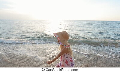 Little girl running along the seashore with walking near...