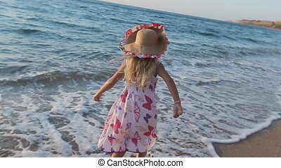 Little girl full of emotions walking along the seashore with her parents in slow motion