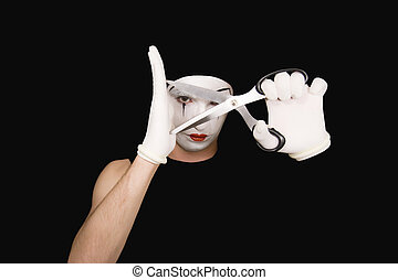 Portrait of mime with scissors on black background