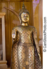 golden buddha statue with the forbidding hand acting -...