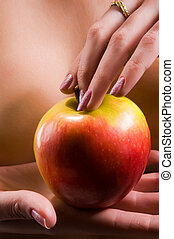 Nude young woman holding apple