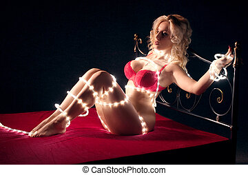 Nude woman with fairy lights laying on bed in darkness