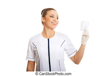 Portrait of female dentist holding a tooth model