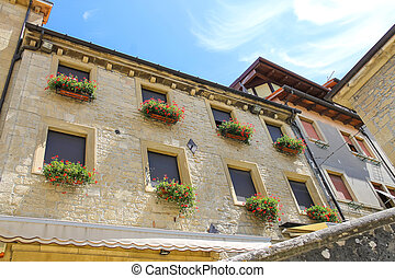 Picturesque house with flowers on windows in the Italian city