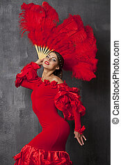 Woman traditional Spanish Flamenco dancer dancing in a red...