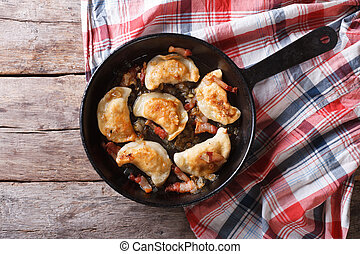 fried dumplings with onion and bacon in a pan horizontal top...