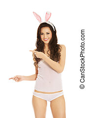 Woman wearing bunny ears and showing copyspace - Beautiful...