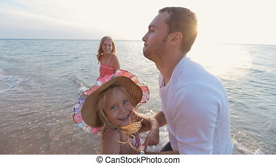 Father picks up the little daughter in straw hat while standing near the sea in slow motion