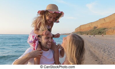 Laughing parents with little daughter sitting on the neck of father walking along the seashore