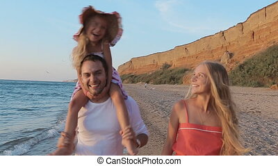 Happy family walks along the seashore