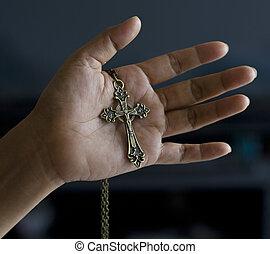 Metallic crucifix in hand