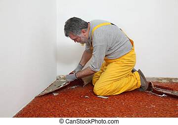 Home renovation, carpet remove - Adult worker removing old...